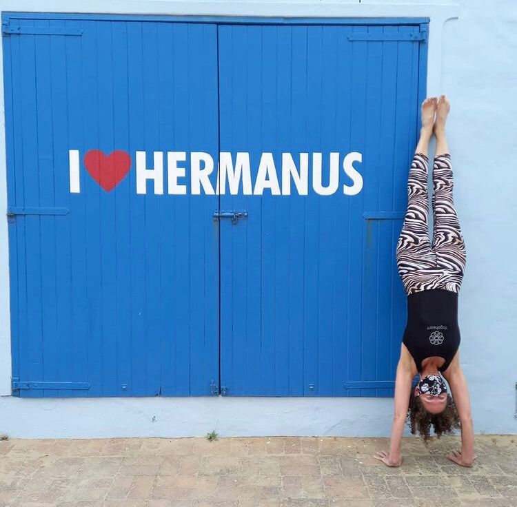Happy acrobat enjoying the blue I Love Hermanus sign, near Cape Town, South Africa