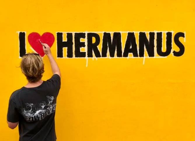 I ❤️ Hermanus painting on yellow wall, near Cape Town, South Africa